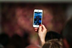 纽约, NY - 9月09日:拿着手机和做图片的客人在奥斯卡De La伦塔时装表演 图库摄影
