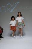 纽约, NY - 10月19日:模型步行在唱腔儿童的衣物预览期间的跑道在petitePARADE哄骗时尚星期 免版税图库摄影