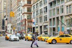 纽约- 2015年3月16日:黄色冲在街市曼哈顿拥挤的街上的出租车和人  图库摄影