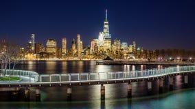纽约财政区摩天大楼和哈得逊河从Hoboken在晚上散步 库存图片