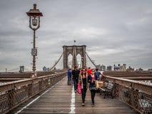 纽约-美国-走在布鲁克林大桥的人们在纽约 库存照片