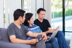 线与多个设备和谈的三个朋友坐沙发 免版税图库摄影