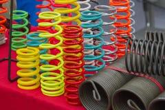 线圈弹簧是在红色桌上的许多颜色 免版税库存图片