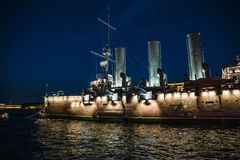 线性巡洋舰极光或Avrora在晚上, 10月革命的标志在俄罗斯 免版税库存照片