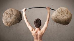 练习大岩石石头举重的皮包骨头的人 图库摄影