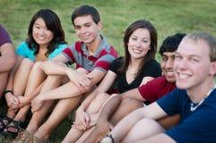 组不同种族的愉快的少年外面 图库摄影