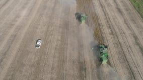 组合横跨在尘土的领域去并且收获秋天大豆庄稼,鸟瞰图种田 股票录像