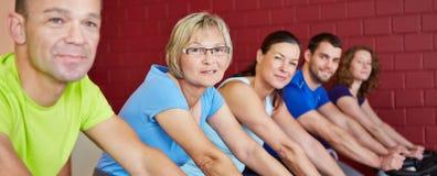 组在健身俱乐部的骑马自行车 免版税库存照片