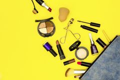 组成与化妆用品的袋子在黄色背景 免版税库存照片