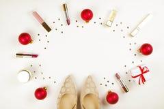 组成与圣诞节装饰的产品和金黄妇女鞋子在与拷贝空间舱内甲板位置的白色背景 免版税库存照片
