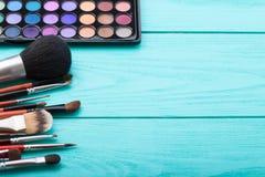 组成产品 眼影和刷子工具 化妆用品和辅助部件在蓝色木背景 顶视图 复制空间 库存图片