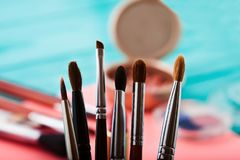 组成产品 眼影和刷子工具 化妆用品和辅助部件在蓝色木背景 顶视图 复制空间 免版税库存照片