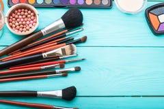 组成刷子和产品 复制空间 嘲笑 化妆用品和辅助部件在蓝色木背景 顶视图 免版税库存照片