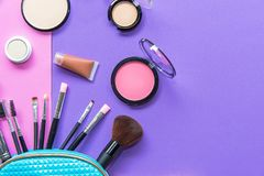 组成溢出在一个淡色蓝色化妆用品袋子外面的产品,在与空的空间的紫色和桃红色背景在边 库存照片