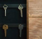 组织您的生活、保险和安全概念:葡萄酒打开了有垂悬在金黄勾子的钥匙的木关键持有人箱子内阁 库存图片
