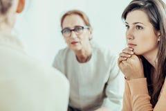细听治疗师的妇女在训练期间女实业家在办公室 免版税库存照片