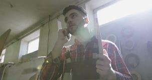 细木工技术制服的一位年轻木匠在一个手机谈话在木材加工产业屋子 股票视频