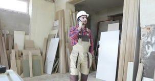 细木工技术制服的一位时髦的木匠和一件白色盔甲谈话在手机在家具工厂 影视素材