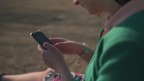 细节关闭突然上升时尚上瘾的年轻女人使用她的电话-发短信和传讯-穿高尔夫球外套和 股票视频