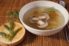 细面条在一个牌照的汤和领域蘑菇在秸杆餐巾 免版税图库摄影