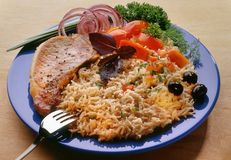 细面条,面条用在一块蓝色板材的猪肉牛排有叉子的,装饰用切的蕃茄 库存图片