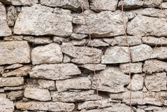 织地不很细背景不规则的自然石墙由与自然植被的元素的不同的石头做成在的 免版税库存照片