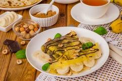 绉纱或薄煎饼与巧克力奶油、香蕉和榛子早餐 库存照片