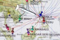 绊倒到有玩具飞机的马尼拉并且推挤在发埃的地图的别针 库存照片