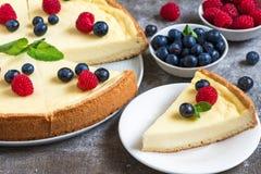 经典之作切了纽约乳酪蛋糕用新鲜的莓果和薄菏在石背景,关闭 库存照片