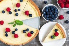 经典之作切了纽约乳酪蛋糕用新鲜的莓果和薄菏在石背景,顶视图 免版税库存照片