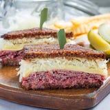 经典之作reuben三明治,供食用泡菜,土豆片,方形的格式 免版税库存照片