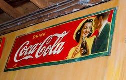 经典可口可乐商标烙记的商标在红色金属板的与减速火箭的样式美国夫妇动画片版本 库存照片
