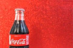 经典可口可乐玻璃瓶有摘要迷离红色闪耀的背景 可口可乐是在商店卖的一碳酸化合的汽水 库存照片