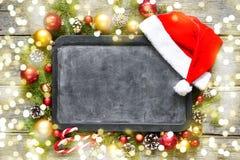 经典圣诞节和新年构成粉笔板,球,玩具,糖果,在葡萄酒木背景的冷杉分支 图库摄影