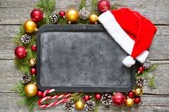 经典圣诞节和新年构成粉笔板,球,玩具,糖果,在葡萄酒木背景的冷杉分支 库存图片