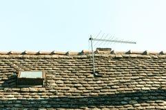 经典在老房子屋顶的葡萄酒模式电视天线有瓦片和窗口的 库存图片