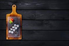 经典寿司卷用在一个木板的虾 顶视图 黑色木背景 免版税库存照片