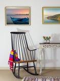 经典摇椅和两本旧书在老牌葡萄酒桌上在米黄墙壁背景有裁减路线的绘画的 免版税库存照片