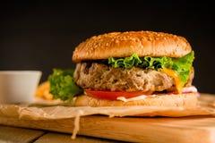 经典汉堡用鲜美牛肉、沙拉、调味汁和蕃茄在黑暗的背景 美国食物 库存照片
