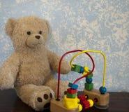 经典玩具熊对有小珠的蓝色墙壁困惑 免版税库存照片