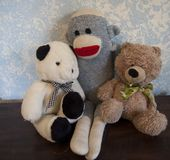 经典玩具熊对有袜子猴子朋友的蓝色墙壁 库存图片