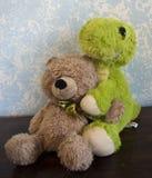 经典玩具熊对有迪诺朋友的蓝色墙壁 免版税库存照片
