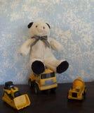 经典玩具熊对蓝色墙壁和经典建筑车 免版税库存照片