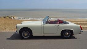 经典白的奶油MG小型汽车在有海的沿海岸区散步停放了在背景中 图库摄影