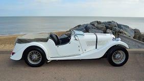 经典白色体育汽车在沿海岸区散步停放了 库存图片
