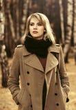 经典米黄外套的年轻时尚妇女走在秋天公园的 免版税库存照片