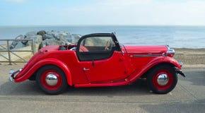 经典红色歌手汽车在有海的沿海岸区散步停放了在背景中 免版税库存照片
