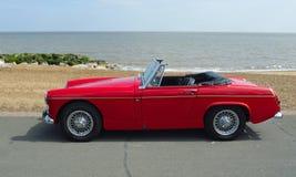 经典红色MG跑车汽车在有海的沿海岸区散步停放了在背景中 图库摄影