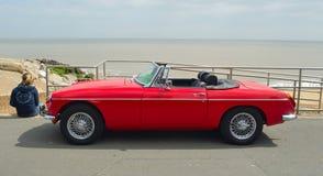 经典红色MG跑车汽车在有海的沿海岸区散步停放了在背景中 免版税库存图片