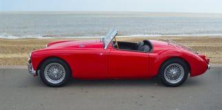 经典红色MGA汽车在有海的沿海岸区散步停放了在背景中 库存图片